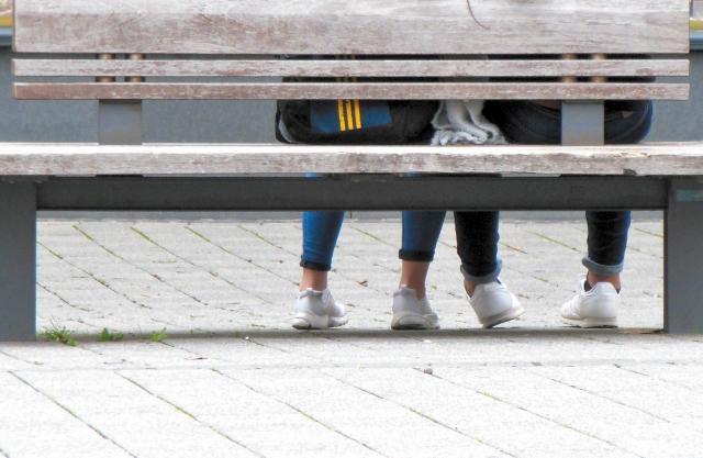 ベンチに座る男女の足もと