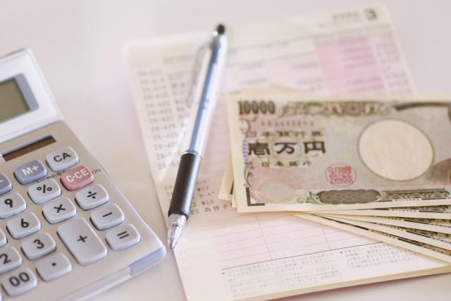 通帳と計算機とペンとお金
