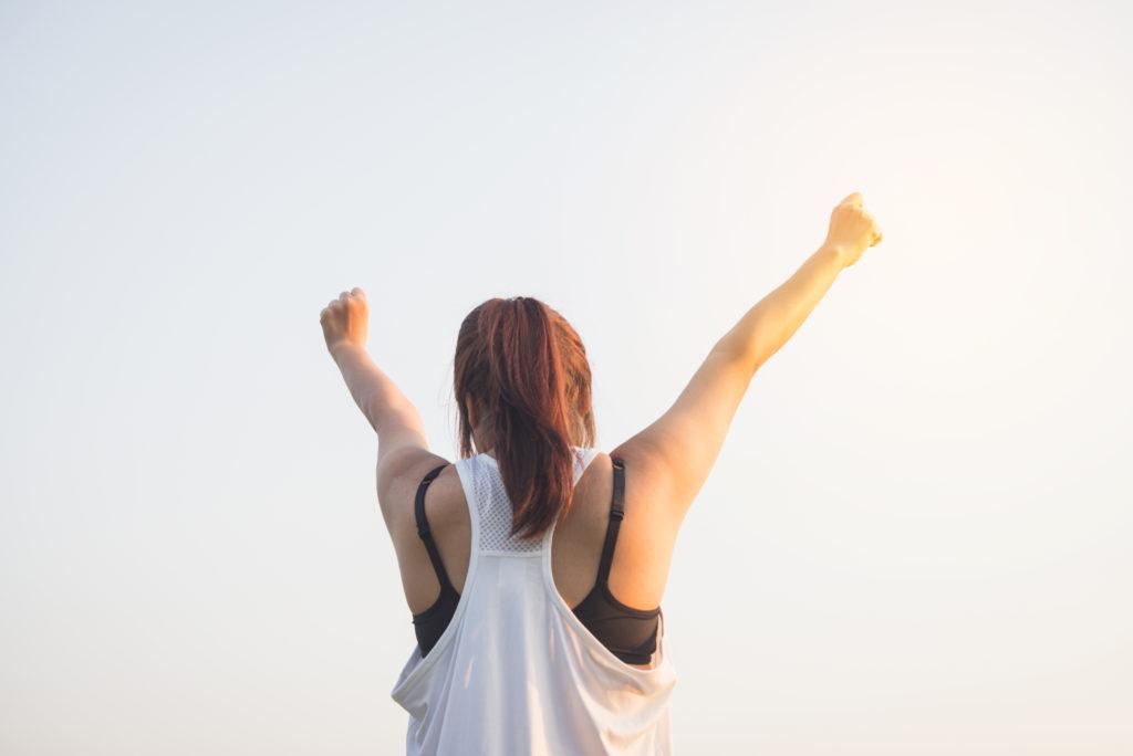 両手を上げ喜ぶ女性の後ろ姿 提供者:Tirachard Kumtanom