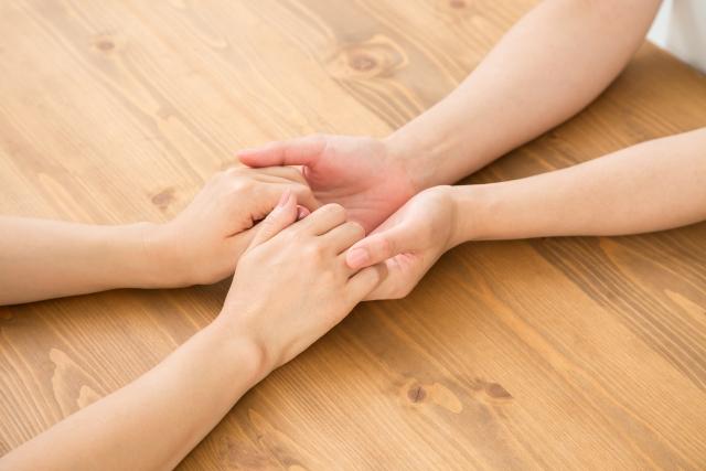 手を取り合う女性ふたり