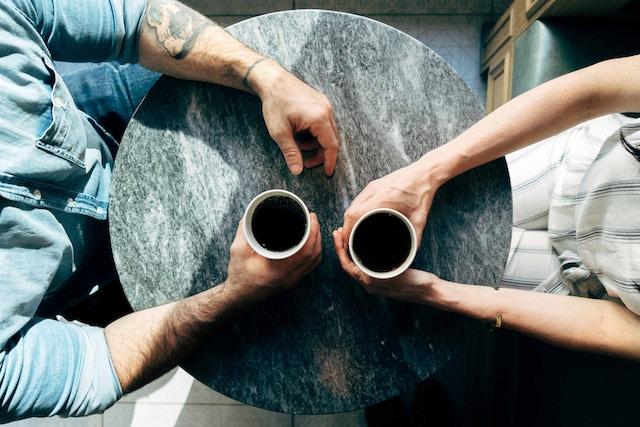 コーヒーを挟む男女