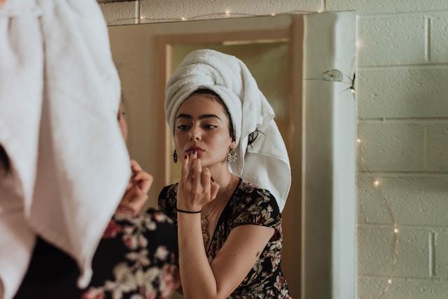 鏡に向かって化粧する女性
