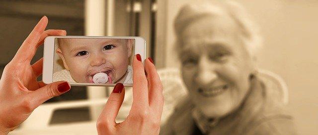 おばあさんとスマホにうつる赤ちゃんの時の姿