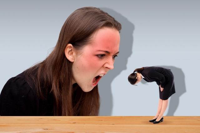大きな女性に叱られる女性