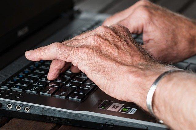タイピングするシニアの手