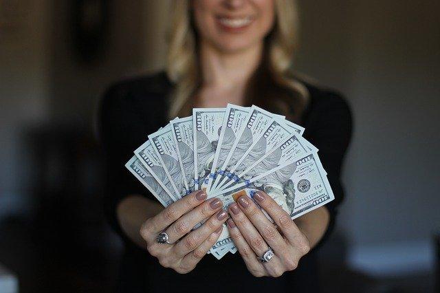 お金を持って笑う女性